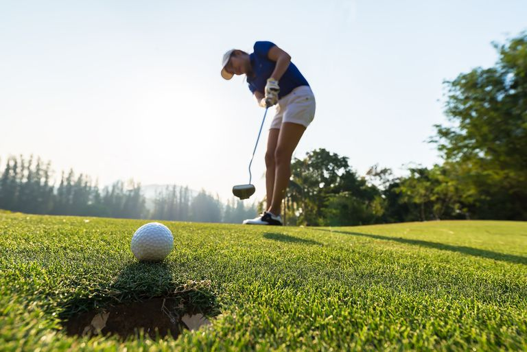 Woman golfer putting the ball into the hole