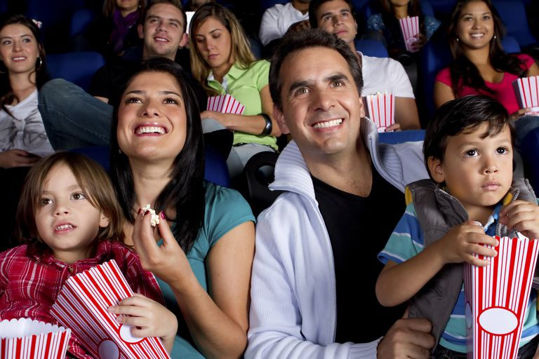 Hispanic family enjoying popcorn at movie theater
