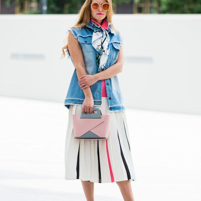 Woman wearing a denim vest and pleated white skirt