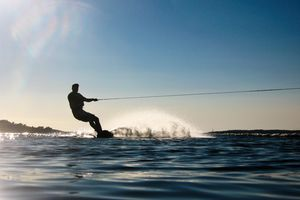 Silhouette man wakeboarding at sea