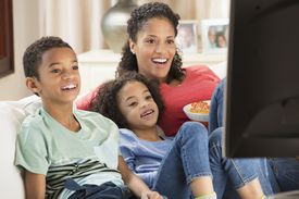 Mixed race family watching television together