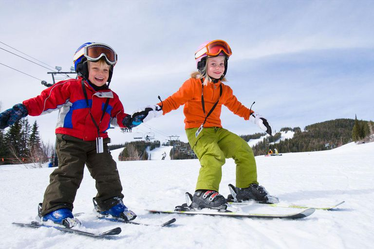 Siblings holding hands and skiing