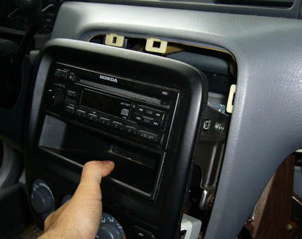 Hand pulling the stereo assembly out of its compartment