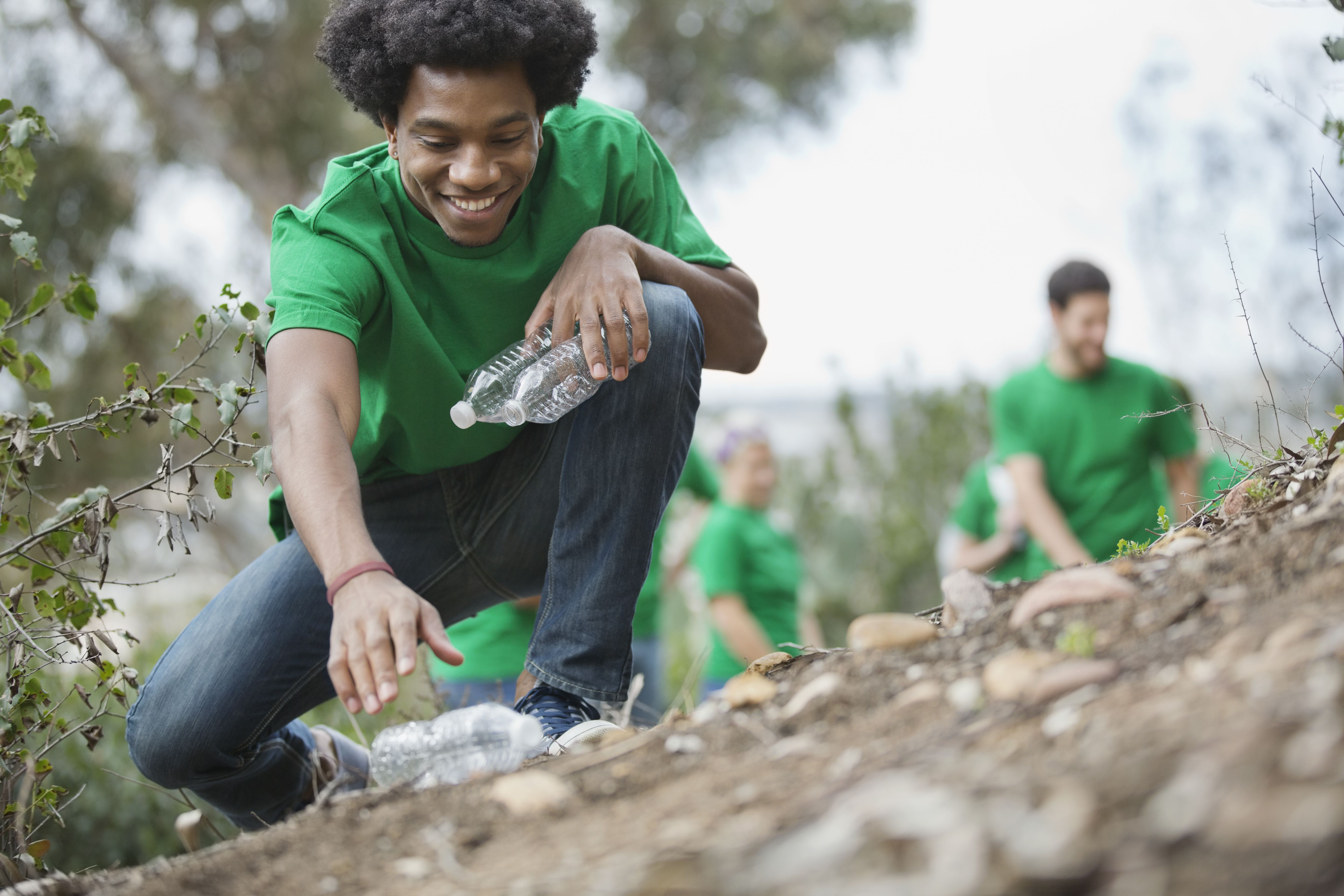 Happy young man picking up empty plastic bottles in park with volunteers in background