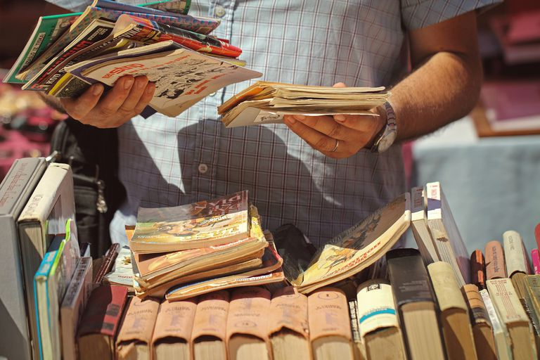 Close-Up Of A Man Holding Books At Flea Market