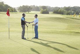 Two golfers shake hands after a match