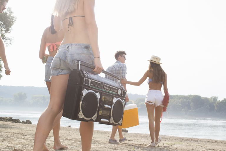 group walking onto a beach with a stereo