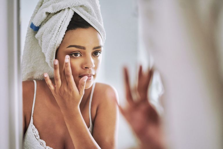 Women applying skincare cream to her face in the mirror