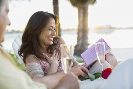 Smiling mature woman reading anniversary card with man on beach