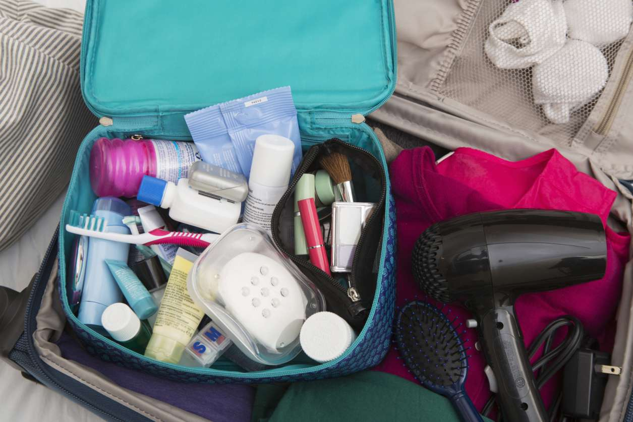 A suitcase with an open toiletry case and blow dryer.