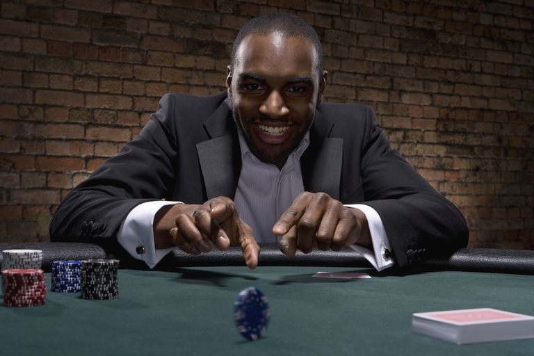 Black man rolling poker chip across poker table