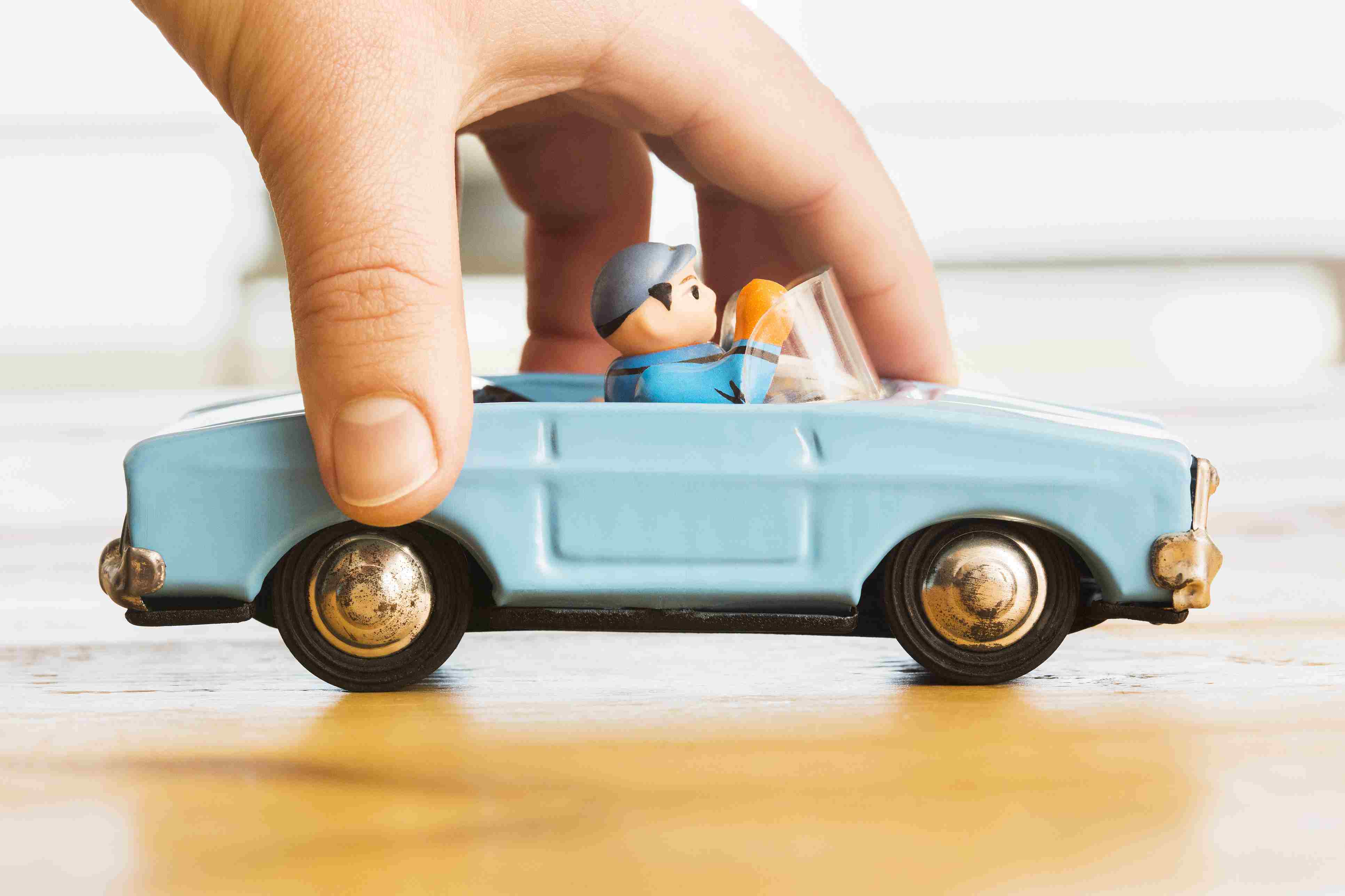 Hand pushing vintage blue toy convertible car