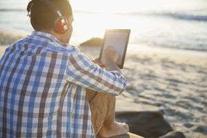 Rear view of young man with headphones using digital tablet at beach