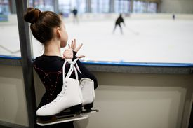 a young girl holding skates at an ice rink