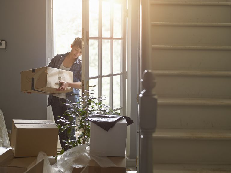Woman carrying a packing box into her new home