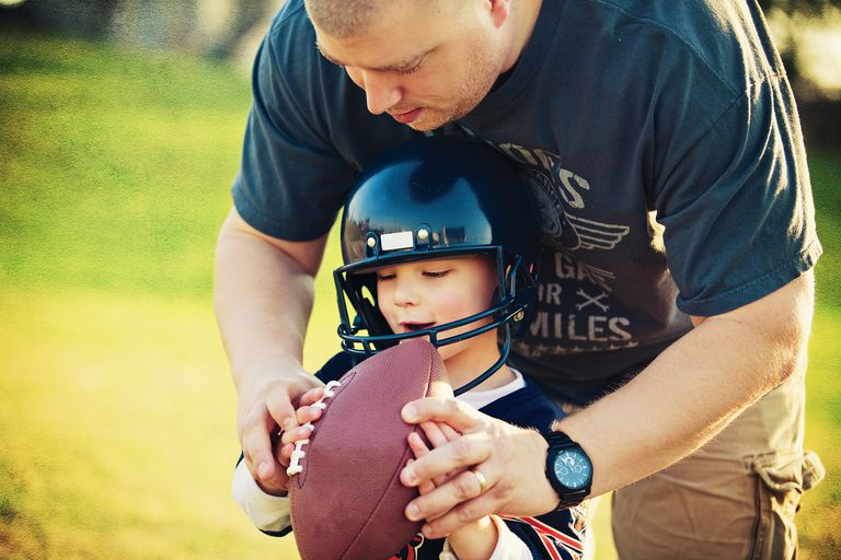 Father teaching young son how to hold a football