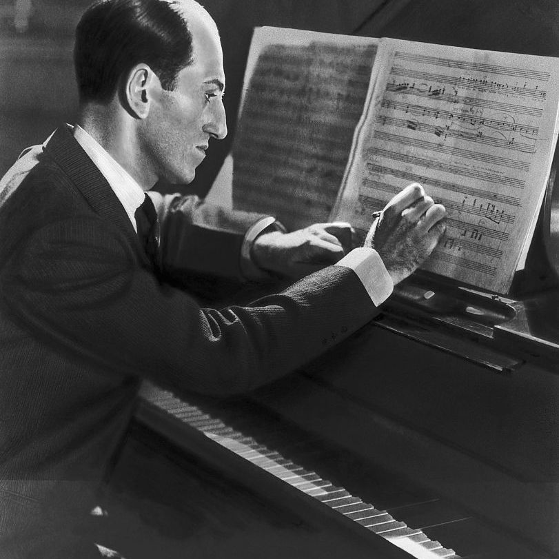 George Gershwin composing a tune at the piano