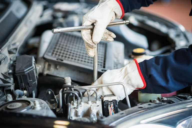 Detail of a mechanic at work on car engine.