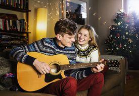man and woman playing acoustic guitar at christmas