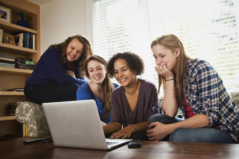 Teen girls sitting on sofa with laptop, laughing