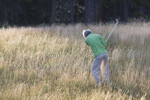 golfer trying to play out of tall grass