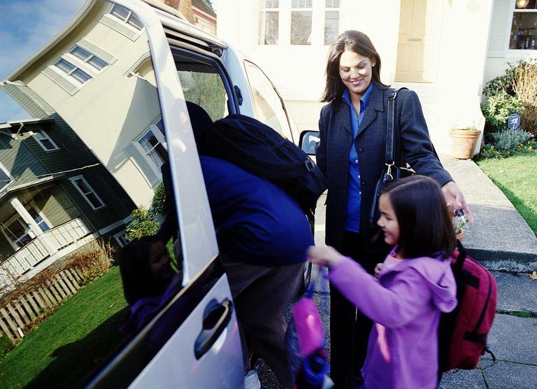 woman helping kids into a minivan