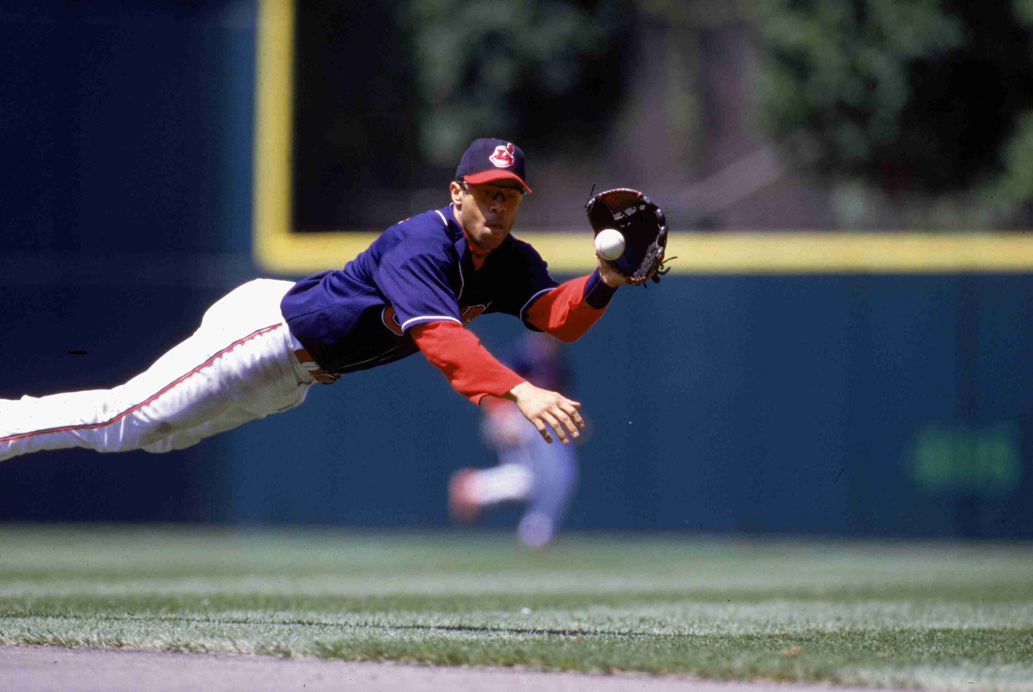CLEVELAND - 2000: Roberto Alomar of the Cleveland Indians dives for a ball during an MLB game at Jacobs Field in Cleveland, Ohio.