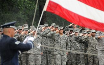 Troops saluting the American flag