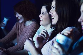 Women laughing in a movie theater