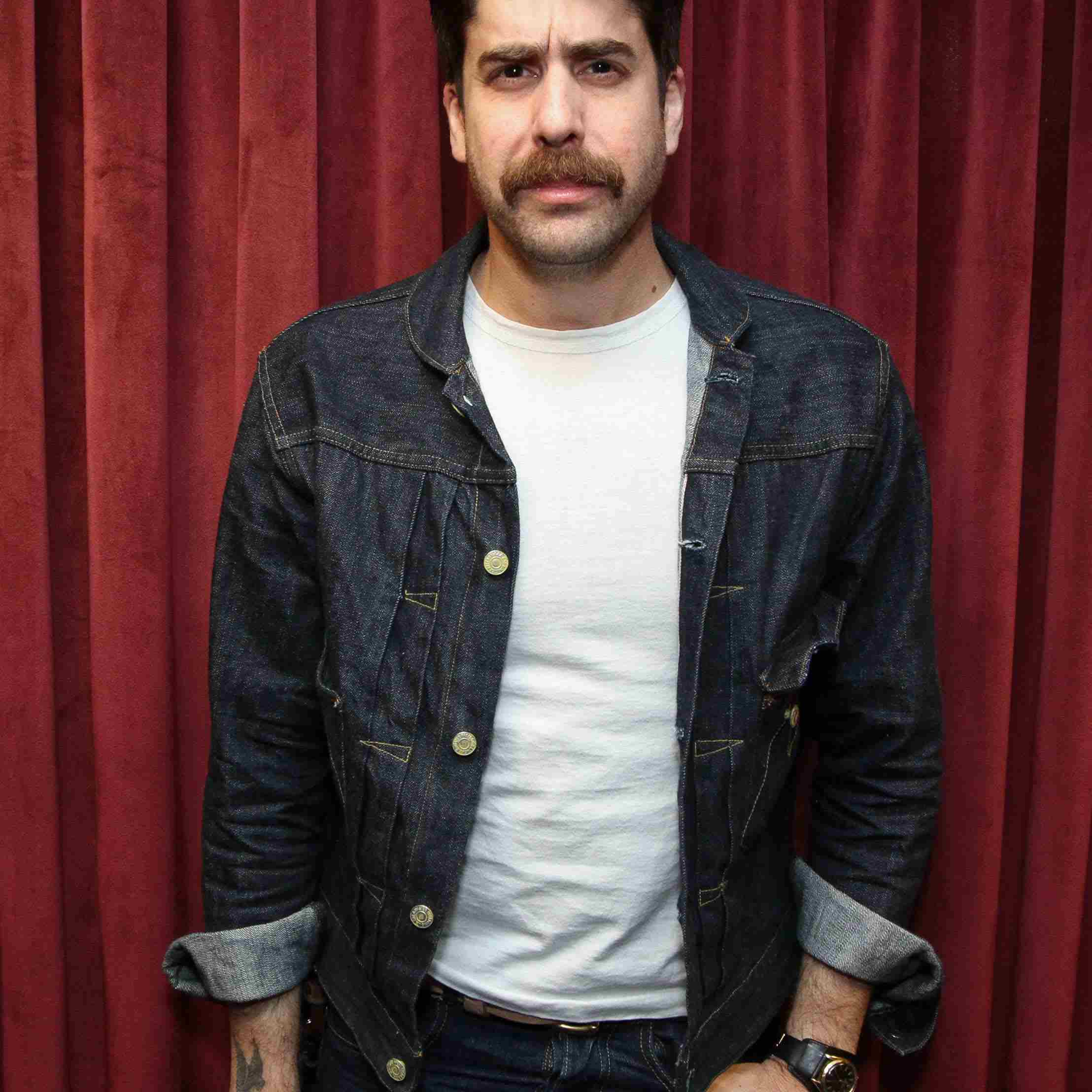 Adam Goldberg in jean jacket in front of red curtains.