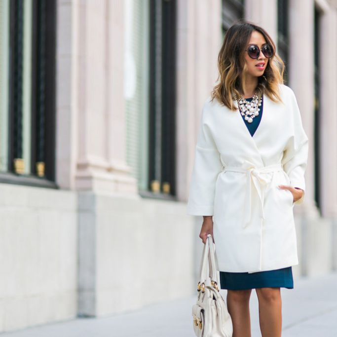 Woman wearing a white trench coat and blue dress with leopard print shoes
