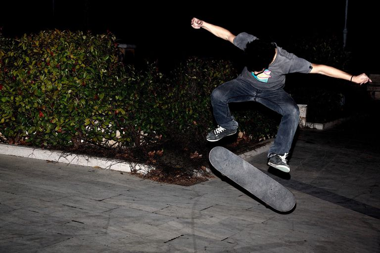 Teenage boy skateboarding at night on concrete footpath