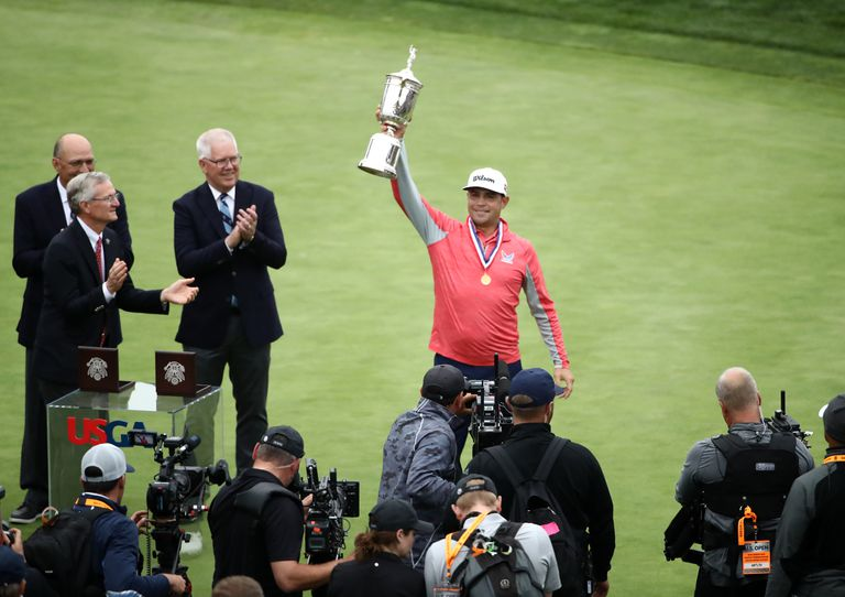 Gary Woodland shows off the trophy he won at the 2019 U.S. Open golf tournament.