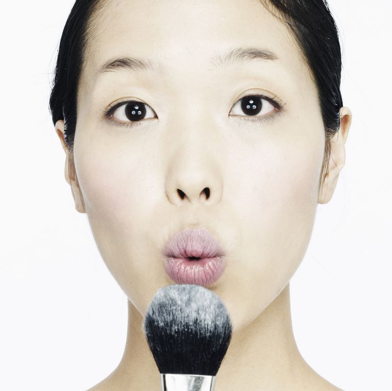 Woman using brush with face powder