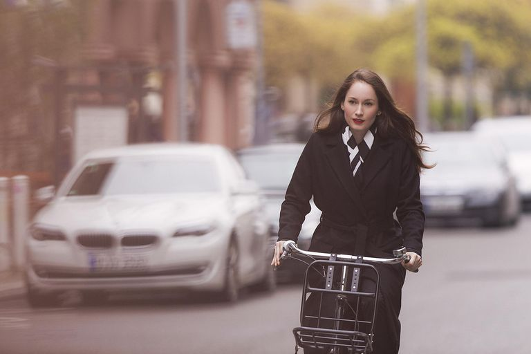 woman in black coat riding bicycle