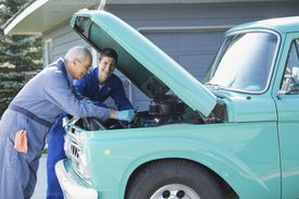 Father and son repairing engine of pick-up truck