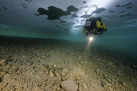 An diver wearing a drysuit dives under ice