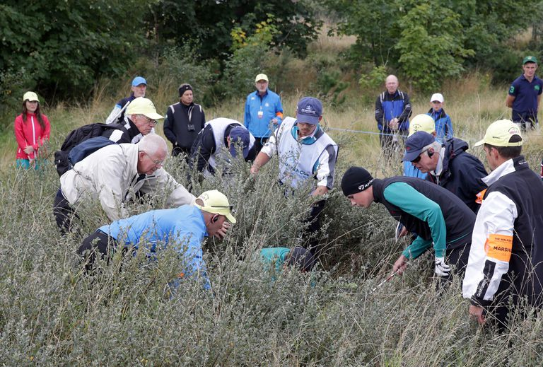 Golfers and fans searching for a lost golf during a Walker Cup match