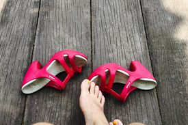 Low Section Of Woman Sitting With Pink High Heels Sandals On Boardwalk