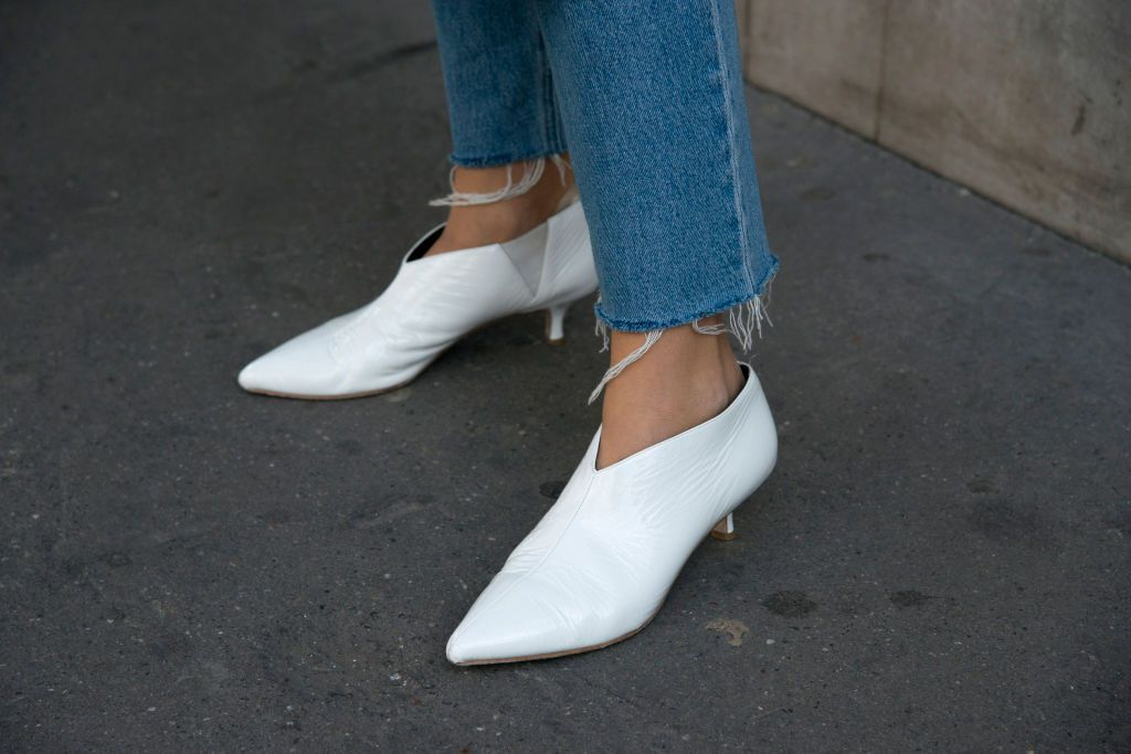 Woman wearing jeans and white ankle boots