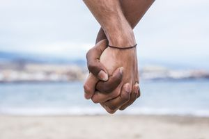 Beige and brown hands clasped together on a romantic beach
