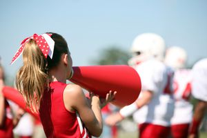 Cheerleader with megaphone cheers for her football team