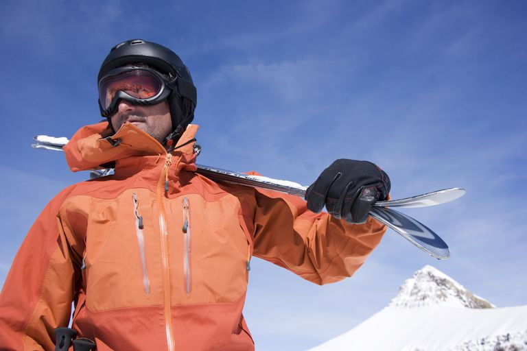 a man on a mountain holding a pair of skis and wearing a coat, gloves, helmet, and goggles