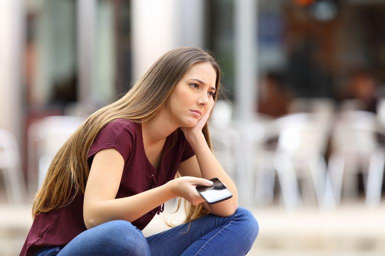 Sad girl waiting for a mobile phone call