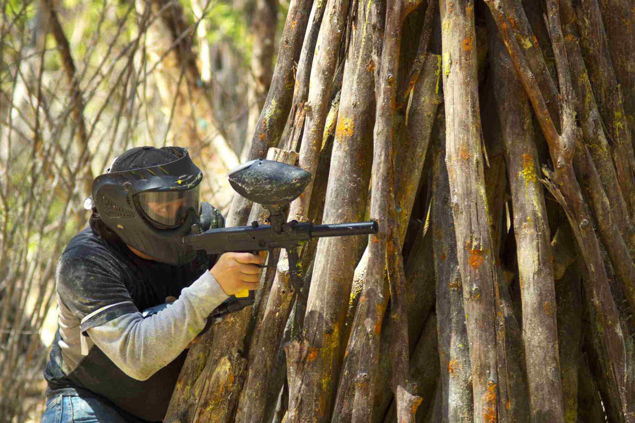 Man hiding with paintball gun and mask
