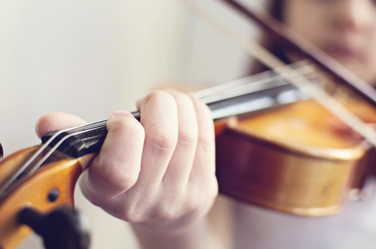 Close up of hand of little girl playing violin
