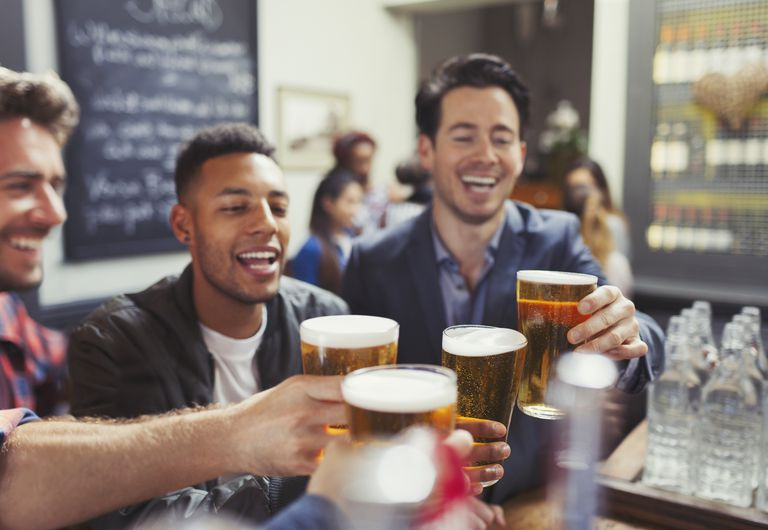 Men friends toasting beer glasses at bar