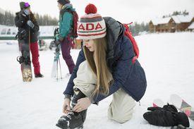 Female snowboarder preparing ski boots, snowboarding with friends at ski resort