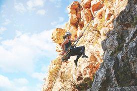 Woman rock climber descending rocks