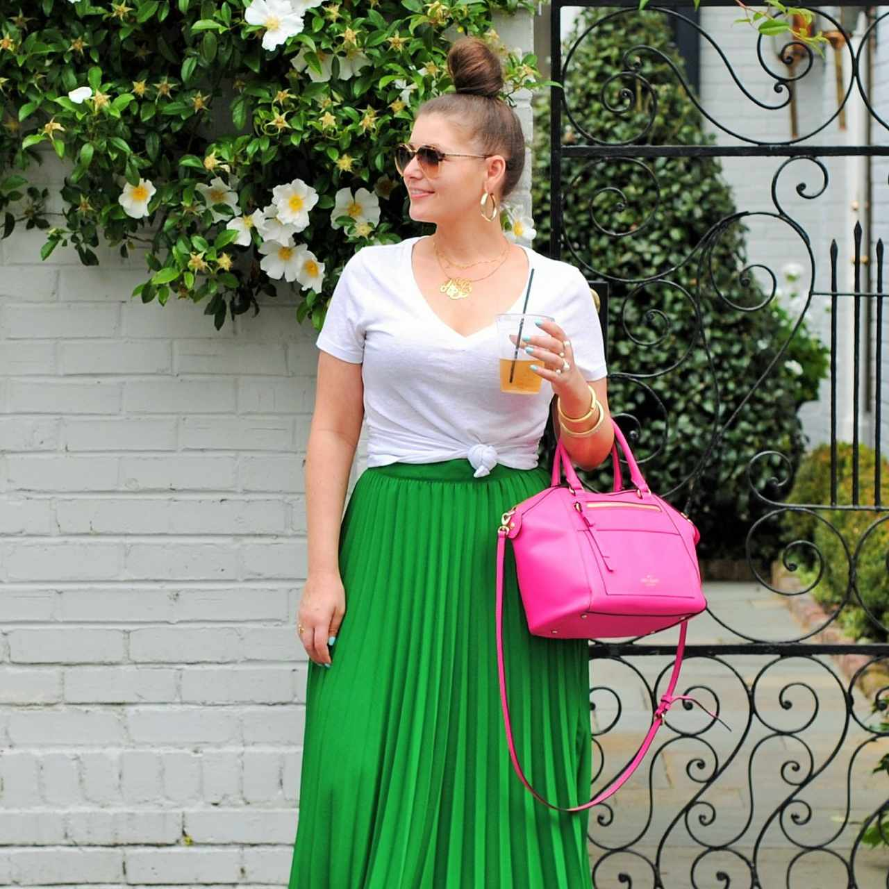 Woman in white t-shirt and green pleated maxi skirt